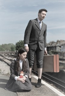 A girl crouches on a railway platform while a boy stands behind her