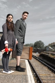 A boy and a girl stand on a railway platform, clutching a doll and suitcase. They are looking down the tracks with worried expressions.
