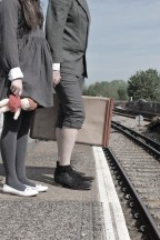 A boy and a girl stand on a railway platform, clutching a doll and suitcase. Their heads are not visible.